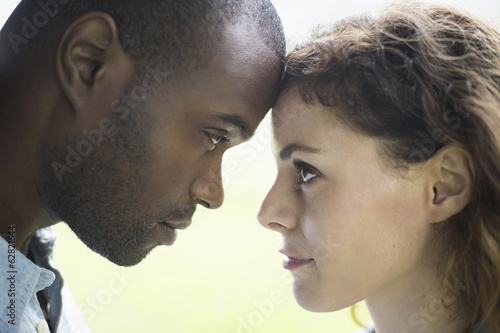 A young man and woman, a couple. Touching foreheads, viewed in profile.