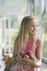 A young girl holding an armful of fresh peaches.