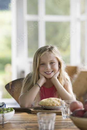A young girl looking at a pastry pie, smiling.