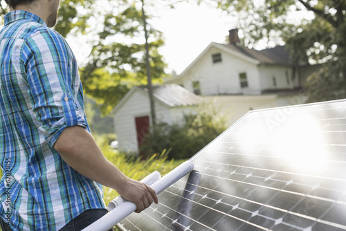 A man using a plan to place a solar panel in a farmhouse garden.