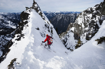 A skier ski-ing down The Slot snow slope on Snoqualmie Peak in the Cascades range, Washington state, USA.