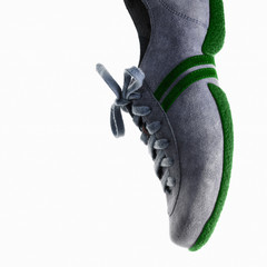 A single sneaker or trainer shoe with laces and green sole.