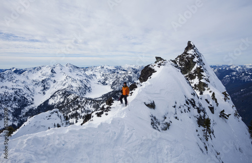 A skier on a ridgeline, pausing before skiing The Slot on Snoqualmie Peak in the Cascades Ranges, Washington state, USA.