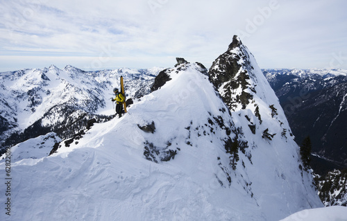 A skier stands on a ridgeline before skiing The Slot on Snoqualmie Peak in the Cascades range, Washington state, USA.