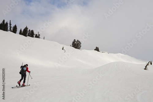A skier skins up a snow slope towards the summit of a mountain peak.