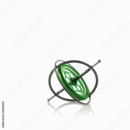 Small metallic object, a gyroscope or spinning wheel with a green patterned centre.