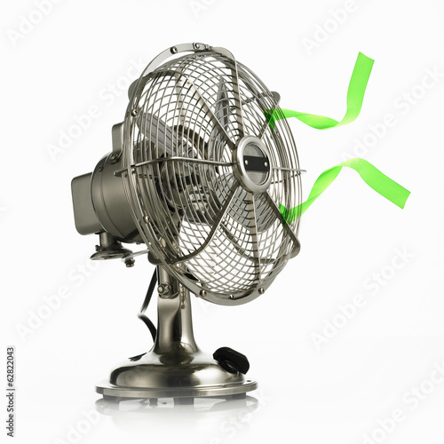 An electric fan with protective cage around the moving parts, and green streamers waving in the breeze.