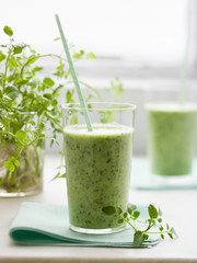 Two glasses of a healthy green smoothie herb drink with a straw.