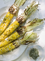 A buffet table set up in a garden for al  fresco meal. Sweetcorn, corn on the cob.