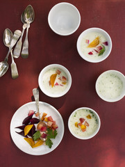 A table laid with small round white china bowls. Fresh food on a red background.
