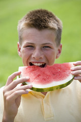 A teenage boy taking a large bite out of a watermelon.