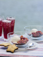 A buffet table set up in a garden for al  fresco meal. Fruit drink. Fresh berries and ice-cream, with baked star biscuits.