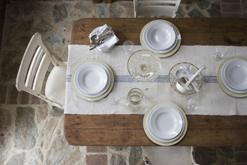 An overhead view of a table laid with white crockery and glassware.