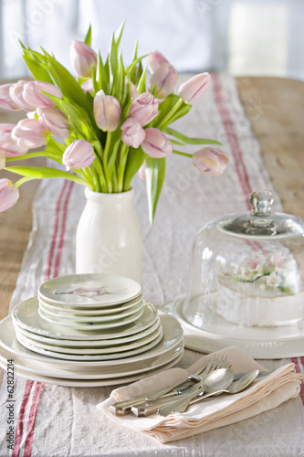 A table laid for a meal with a vase of pink tulips.
