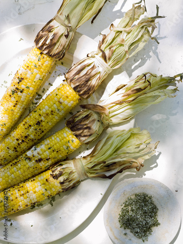 A buffet table set up in a garden for al  fresco meal. Sweetcorn, grilled corn on the cob.