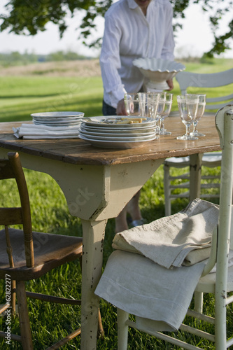 A table laid in a garden, with white china crockery and cutlery. Summer.