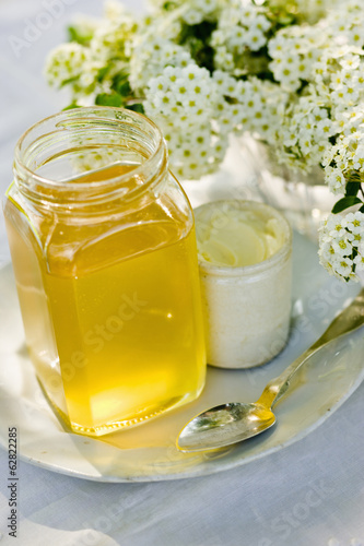 A vase of fresh flowers, a jug of cream and a pot of honey on a table.