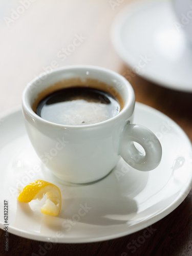 A cup of black coffee in a white china cup with a small twist of lemon peel in the saucer.