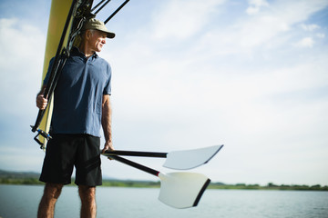 A middle-aged man carrying oars and a rowing shell on his shoulder.
