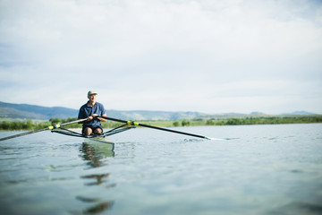 A man in a rowing boat using the oars.
