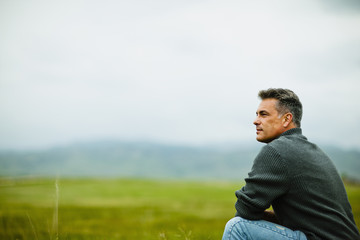 A man sitting alone looking into the distance, deep in thought.
