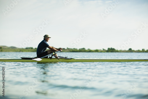 A middle-aged man in a rowing boat on the water.