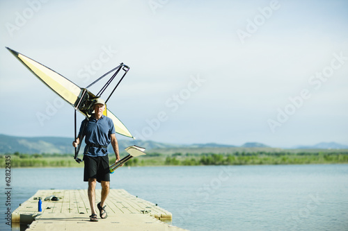 A middle-aged man carrying oars and a rowing shell on his shoulders, on a pontoon.