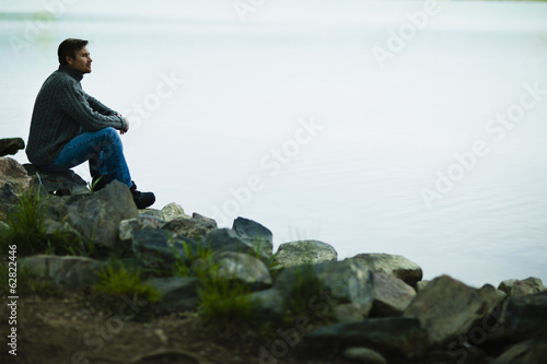 A middle-aged man sitting on rocks looking pensively over the water.