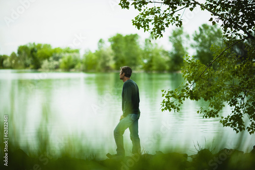 A man standing alone looking into the distance across the water, deep in thought.