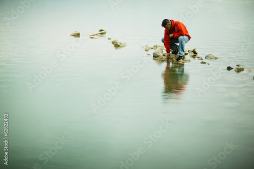 A man in a red jacket balanced in a contemplative pose on a stepping stone or rock in shallow water.