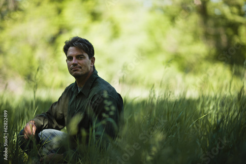 A man outdoors, sitting on the ground, looking thoughtful and contemplative.