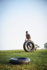 A teenage boy running across the grass rolling a swim float, black tyre in front of him.