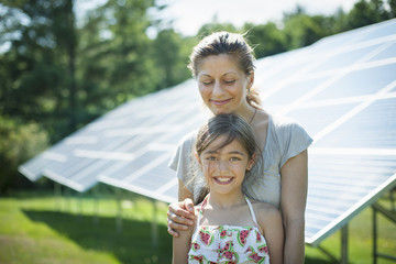 A child and her mother in the fresh open air, beside solar panels on a sunny day at a farm in New York State, USA.