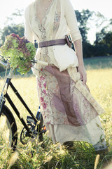 A girl in vintage clothing, paisley patterned cotton skirt with a bicycle in long grass.