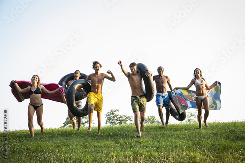 A group of teenagers, boys and girls, running across the grass holding swim towels and inflated floats.