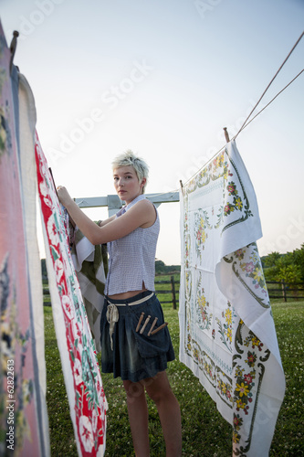 A young girl, teenager, hanging out the washing, pegging patterns fabric sheets to a washing line.