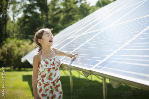 A child in the fresh open air on a sunny day, beside solar panels at a farm in New York State, USA.