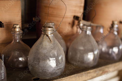 A row of glass jars, with stoppers and large clay pots on a shelf.