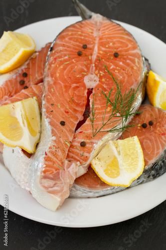 salmon on white plate on black background