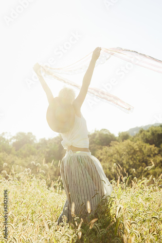 A beautiful girl dancing and waving scarves around her head in the open air.