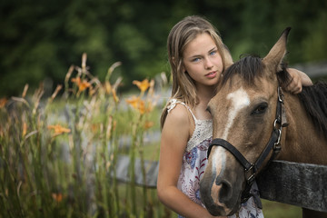 A young girl with a pony wearing a halter, in a field full of wild flowers and grasses.