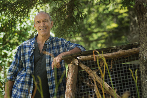 A traditional organic farm in the USA, and a man leaning against a fence.