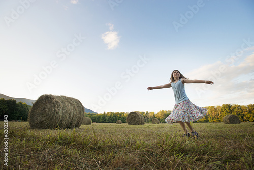 A field full of tall rounded hay bales, and a young girl dancing with her arms outstretched on the stubble field.