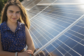A young woman standing beside and leaning against a large solar panel installation.