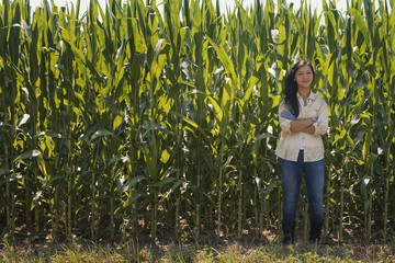 A young woman standing with arms folded, in front of a very tall maize, corn crop in the field.