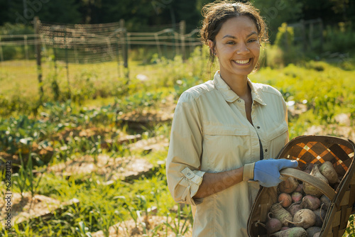 A woman carrying a basket of freshly gathered vegetables and root crops.