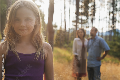 A young girl with long blonde hair in woodland in the fresh air.