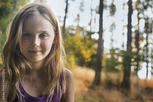A young girl with long blonde hair in woodland in the fresh air, looking at the camera.