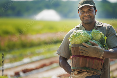 A man holding a basket of freshly harvested vegetables.