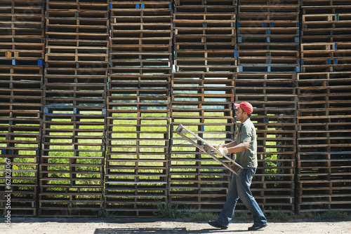 A man carrying a wooden plant frame or pallet in front of a huge stack of objects.